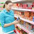 женщина читает состав продуктов, чтобы найти пищевые добавки